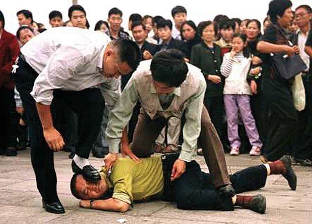 La police arrête un manifestant du Falun Gong sur la place Tiananmen le 1er octobre 2000.