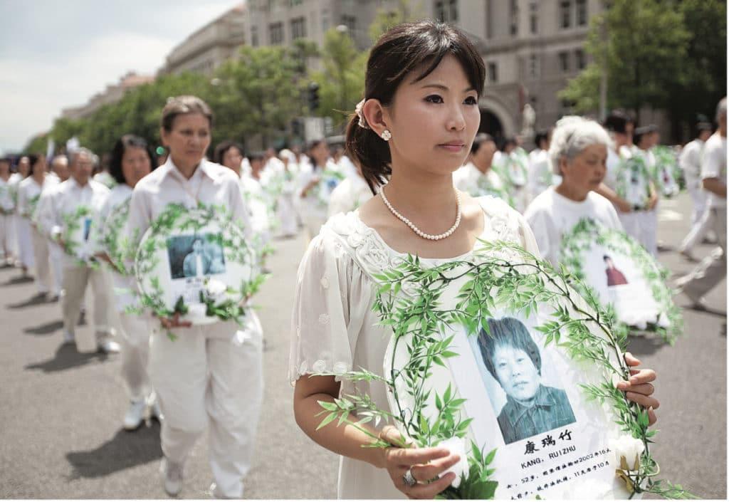 Des pratiquants de falun gong  résistant pacifiquement en tenant des photos de victimes de la persécution.